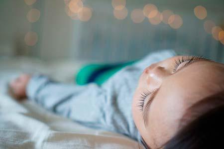 Un bebé durmiendo en la cama